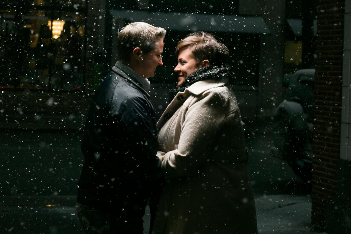 same sex couple engagement session in a snowy blizard