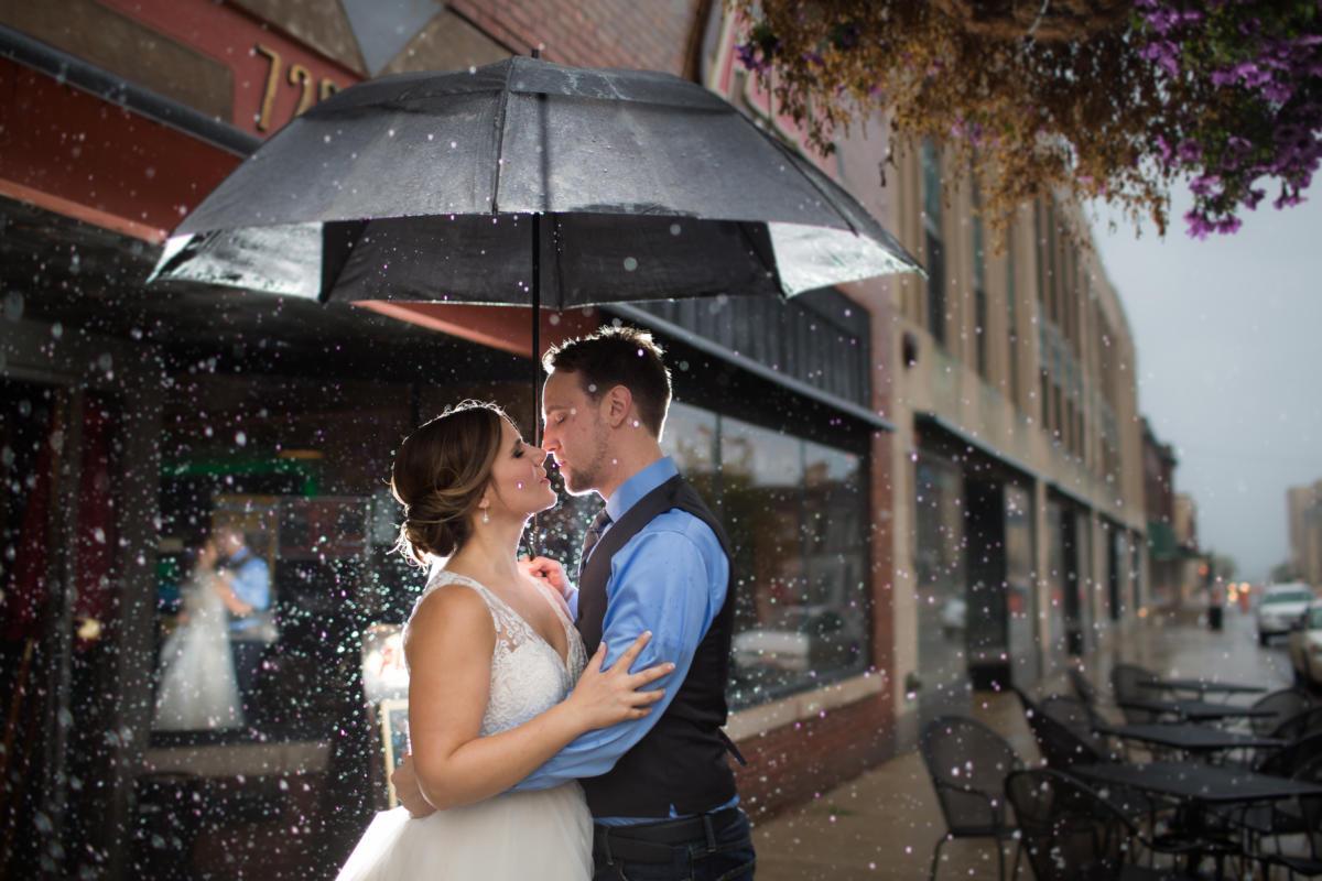 wedding couple under umbrella on rainy day