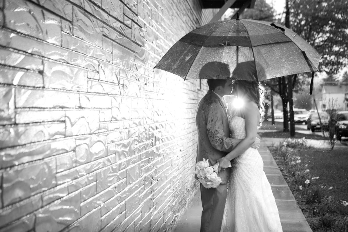 black and white photo of a couple standing under a black umbrella in the rain